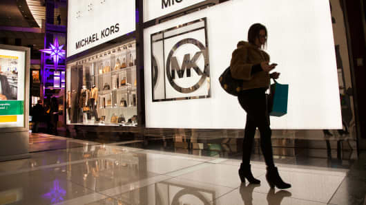A pedestrian passes by a Michael Kors retail store in New York.