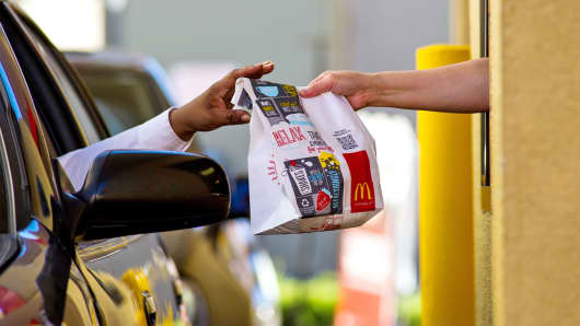 A customer receives an order from an employee at the drive-thru of a McDonald's Corp. restaurant in San Pablo, California, U.S.