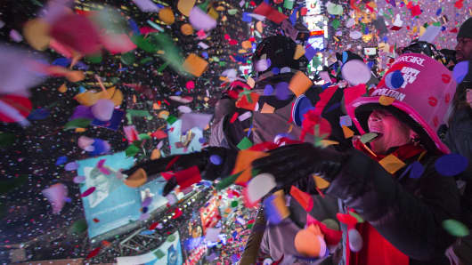 Revelers toss confetti over Times Square from a hotel balcony as the clock strikes midnight during New Year's Eve celebrations in New York, Jan. 1, 2015.
