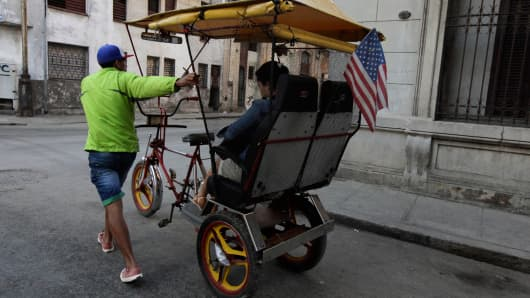 A man pushes his tricycle taxi with a U.S flag on a street in Havana December 18, 2014.