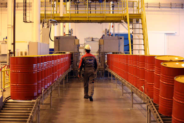 An employee walks between lines of oil barrels at a Royal Dutch Shell Plc plant.