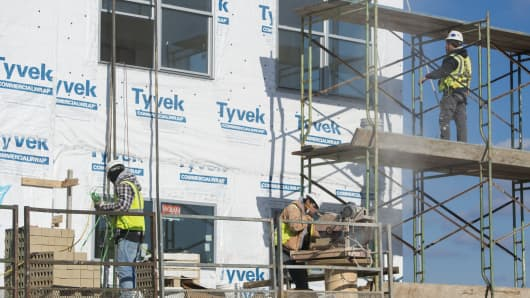 Construction workers build an apartment building in Alexandria, Virginia, December 30, 2014.