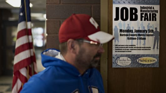 A man walks past a sign at the entrance to a Princeton Area Chamber of Commerce job fair in Princeton, Illinois.