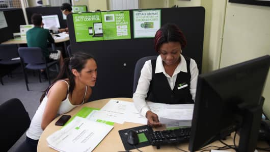 An H&R Block tax associate assists a client with her taxes.