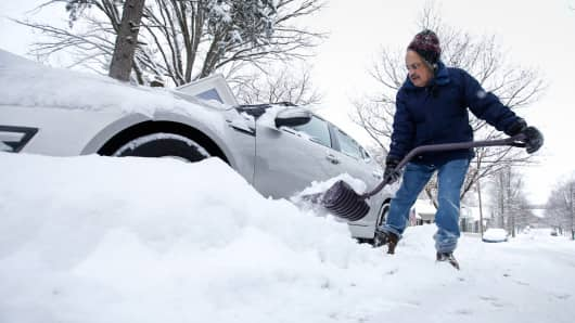 A man removes snow from around his car yesterday in Zionsville, Ind.