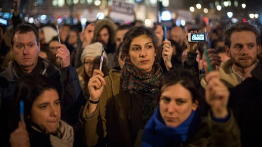 People hold pens aloft during a vigil in Trafalgar Square in London for victims of the terrorist attack in Paris on January 7, 2015.