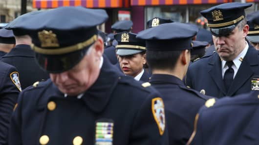 Some with backs turned, New York City police attend a funeral service for slain officer Wenjian Liu, January 4, 2015 in New York City.