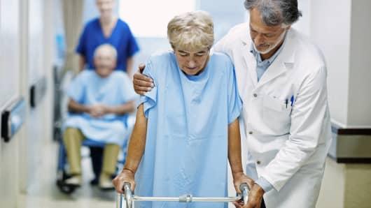 Doctor assisting elderly patient
