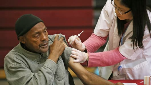 A man receives a flu shot from a Walgreens employee during a free flu shot clinic at Allen Temple Baptist Church in Oakland, Calif.