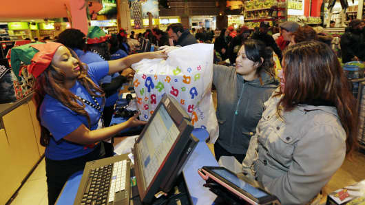 Employees assist shoppers at the check-out counter of a Toys R Us Inc. store in New York.