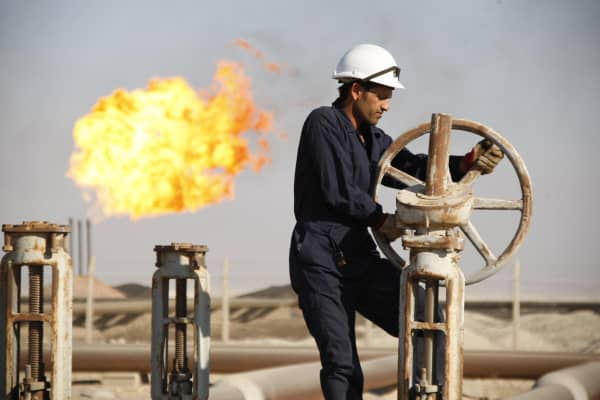 A worker adjusts the valve of an oil pipe at West Qurna oilfield in Iraq's southern province of Basra.