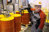 Employee filling barrels with oil