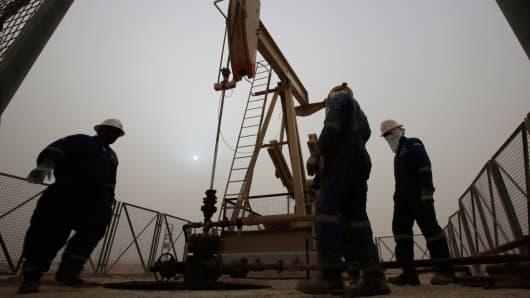 Men work on an oil pump during a sandstorm in the desert oil fields of Sakhir, Bahrain, January, 2015.