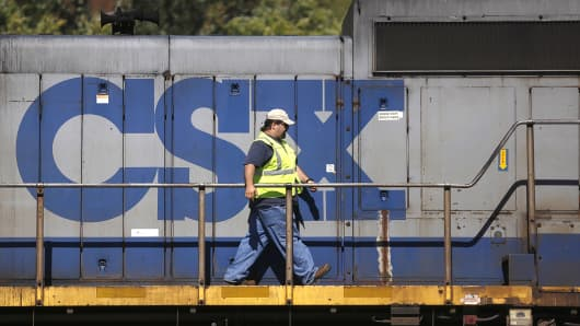 A CSX employee walks on a locomotive while on a siding at Worthville, Ky., Oct. 11, 2013.