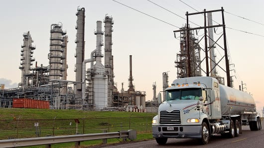 Tanker truck driving past oil refinery