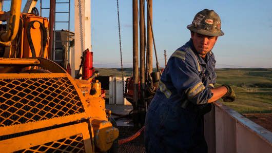 A worker pauses while drilling for oil on a derrick in the Bakken shale formation outside Watford City, North Dakota.