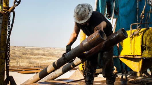 A worker at Endeavor Energy Resources LP's Big Dog Drilling Rig 22 in the Permian Basin outside Midland, Texas, on Dec. 12, 2014.