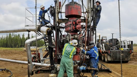 Roughnecks build a drilling rig on an oil field at the MEG Energy site near Fort McMurray, Alberta, Canada.