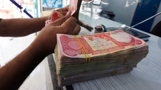 A customer counts Iraqi dinars at a money changer in Baghdad.