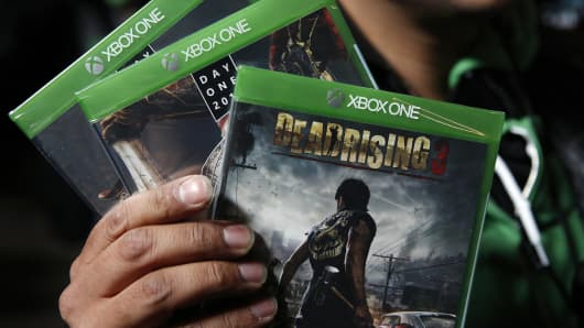 A customer poses with three new Xbox One video games after purchasing them in Los Angeles.