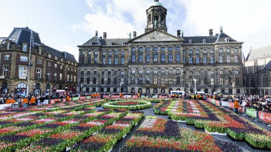 People attend Dutch National Tulip Day in front of the Royal Palace at Dam Square, in Amsterdam, Netherlands.