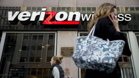 A pedestrian talks on a mobile phone as she walks past a Verizon Wireless retail store in Washington, D.C.