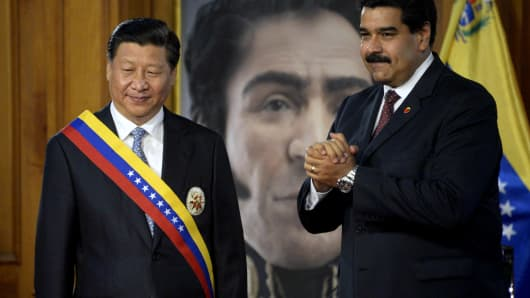 Venezuelan President Nicolas Maduro (R) gestures after decorating China's President Xi Jinping (L) with a Venezuelan sash during an official visit in Miraflores Presidential Palace, Caracas on July 20, 2014.