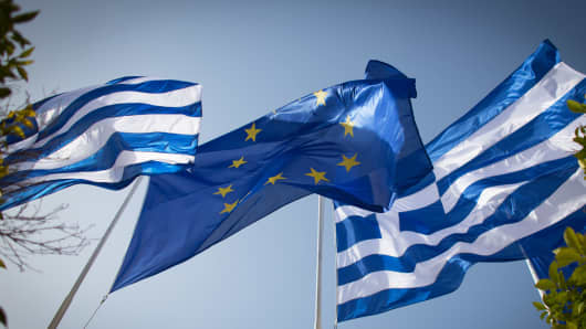 The national flag of Greece and the flag of the European Union fly above a government building in Athens.