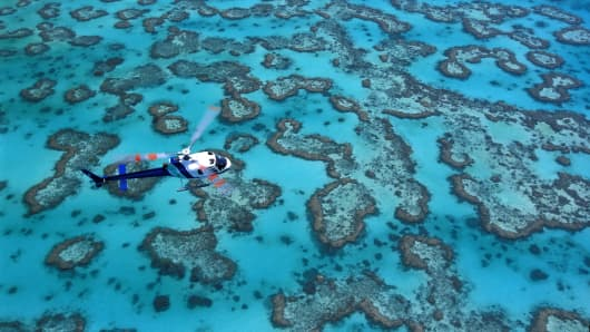 A helicopter flies over the Great Barrier Reef near Heron Island, Australia.