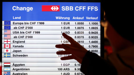 A man looks at a board showing currency exchange rates in Bern January 15, 2015.
