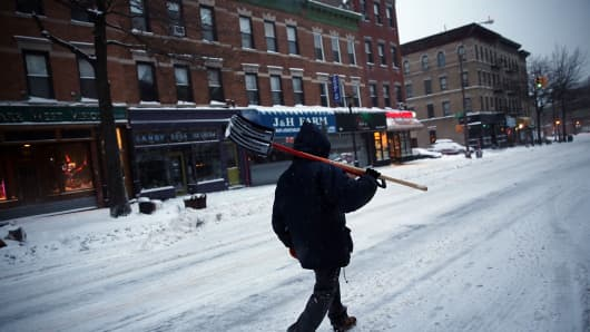 A man walking with a shovel in Brooklyn, New York the morning after a major winter storm on January 27, 2015.