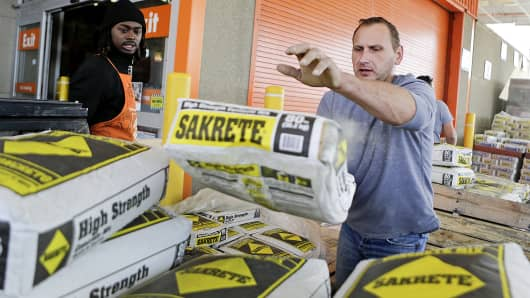 Customer Jacek Mroczkowski tosses bags of concrete mix into his truck at a Home Depot store in Washington.