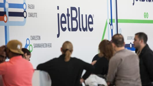 Customers check in at the JetBlue counter at John F. Kennedy Airport