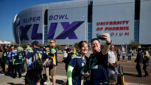 Fans gather outside of University of Phoenix Stadium prior to Super Bowl XLIX between the Seattle Seahawks and the New England Patriots on February 1, 2015 in Glendale, Arizona.