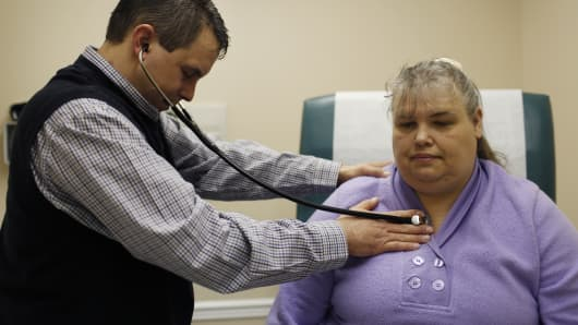 A doctor listens to the heartbeat of a patient during her appointment at the Breathitt County Family Health Center in Jackson, Ky. Despite suffering from a past heart attack and diabetes Blair was able to receive medical coverage through Medicaid expansion under the Affordable Care Act.