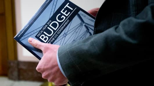 A staff member carries a copy of President Barack Obama's Fiscal Year 2016 Budget outside the Senate Budget Committee hearing room in Washington, D.C., U.S., on Monday, Feb. 2, 2015.