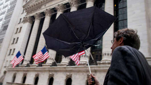 A man struggles with his umbrella as he passes by the New York Stock Exchange in New York February 2, 2015.
