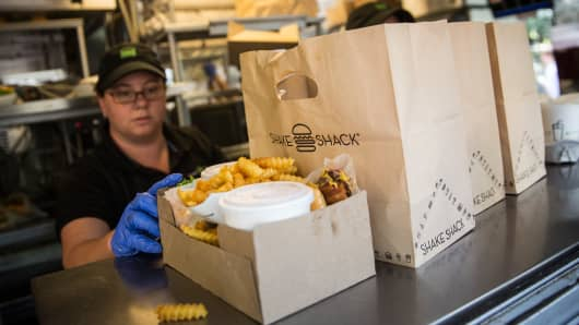 Shake Shack workers prepare orders on August 18, 2014 in Madison Square Park in New York City. Shake Shack is allegedly considering going public and holding an initial price offering (IPO).