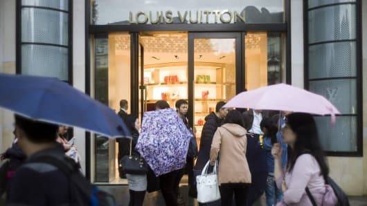 Asian tourists stand in front of the Louis Vuitton shop on the Champs-Elysees in Paris.
