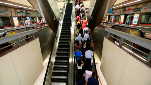 Commuters walk up an escalator inside the Raffles Place MRT station during rush hour at the central business district area in Singapore.