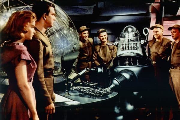 "Anne Francis and Leslie Nielsen watch as the robot takes the controls of the spaceship in a scene from the film ""Forbidden Planet."""