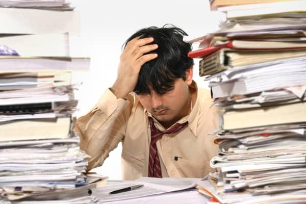 Man confused desk overwhelmed