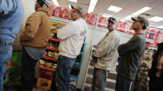 Men employed in the oil industry wait in line for food at a service station in Odessa, Texas on February 4, 2015.