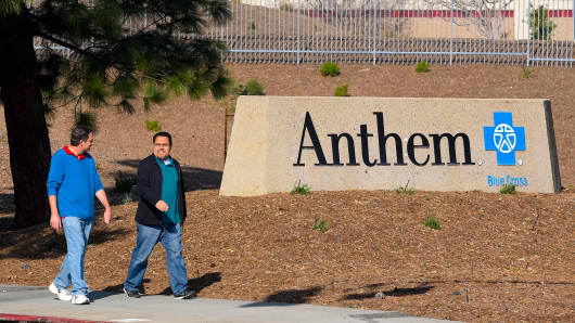 People walk past an office building of health insurer Anthem in Los Angeles.