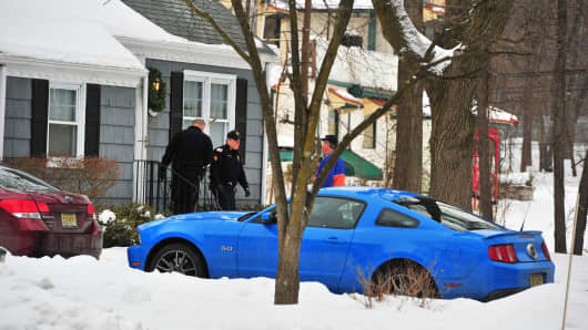Police stand outside the house in Closter, N.J., Feb. 7, 2015 where a couple was found dead in a possible murder-suicide.