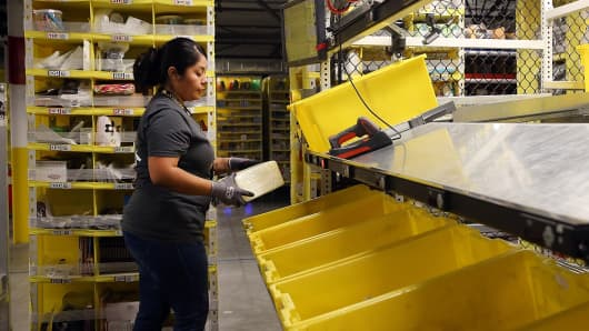 An Amazon.com worker picks orders at an Amazon fulfillment center in Tracy, Calif.
