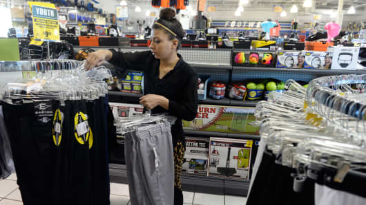 A sales clerk stocks baseball uniforms and gear at the Big 5 Sporting Goods store in Denver.