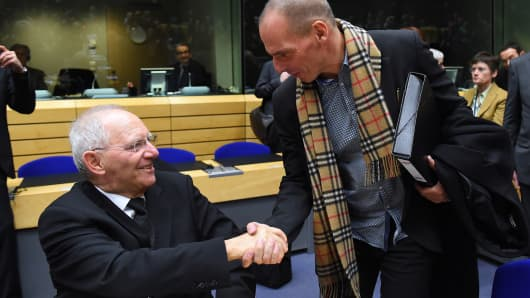 Greek Finance minister Yanis Varoufakis shakes hands with German Finance Minister Wolfgang Schauble during the Eurogroup finance ministers meeting on February 11, 2015