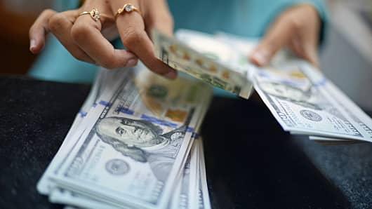 Currency exchange clerk counting U.S. dollars
