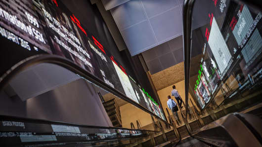 Pedestrians exit an escalator that runs past an electronic screen and ticker board that indicates stock figures at the Singapore Exchange Ltd. (SGX) headquarters.